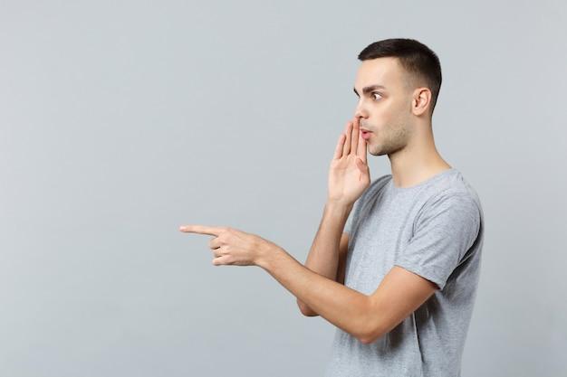 옆으로 검지 손가락을 가리키는 그의 손 뒤에 비밀을 속삭이는 캐주얼 옷에 놀란 젊은 남자의 측면보기