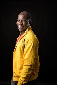 カメラを見て立って、黒い背景に笑みを浮かべてアフリカ系アメリカ人男性の側面図