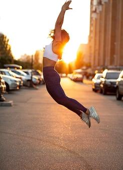 금빛 저녁 햇살 아래 거리에서 뛰는 운동하는 젊은 여성의 옆모습