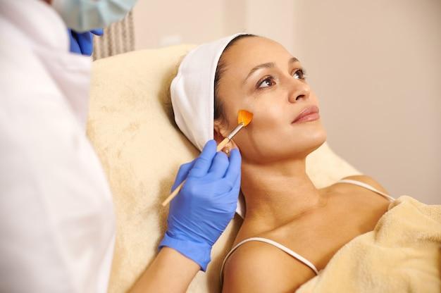 Вид сбоку на привлекательную латиноамериканскую женщину, лежащую на массажном столе, и руку косметолога, держащую косметическую кисть возле ее лица