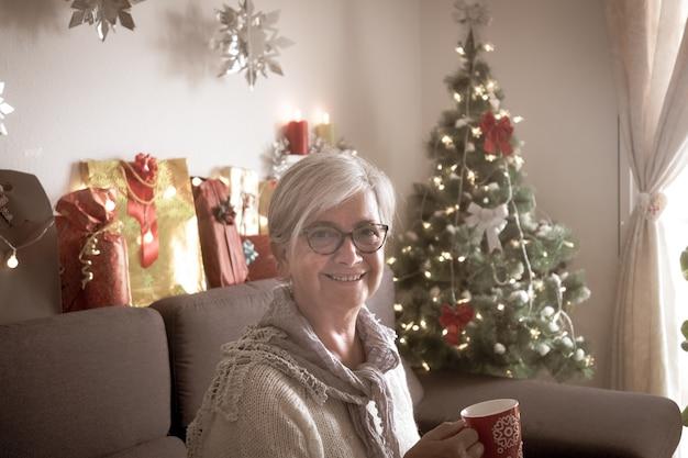 クリスマスツリーとプレゼントを背景にソファに座っている白髪の老婆の側面図。お茶を飲みながらリラックスする1人の高齢者