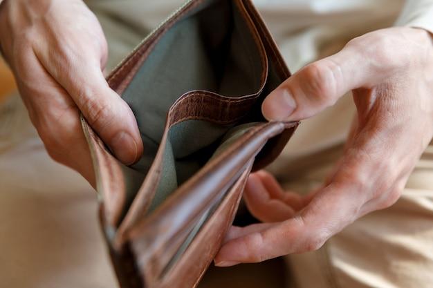 人の手にある空の財布の側面図。経済・金融の倒産・倒産 お金がない人