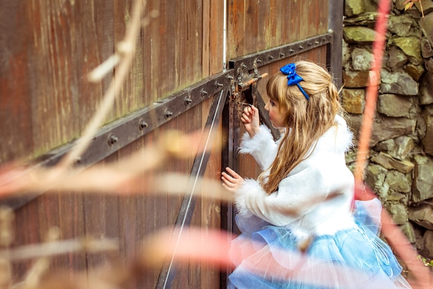 門の鍵穴を覗く風景の中の小さな美しい少女の側面図