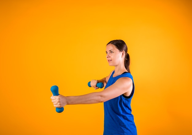 テキスト用のスペースとオレンジ色の壁にダンベルとスポーツウーマンの側面図