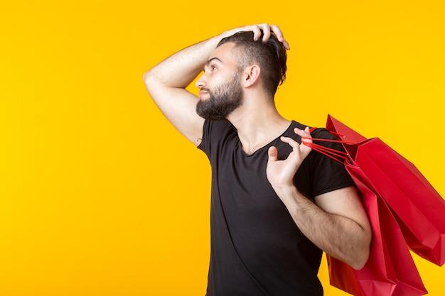 Вид сбоку на расстроенного молодого бородатого стильного хипстера, держащего сумки с покупками, позирующего на желтом