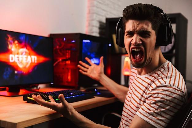 Злой геймер, играющий в видеоигры на компьютере, вид сбоку