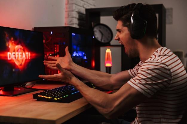 Вид сбоку сердитого кричащего геймера, играющего в видеоигры