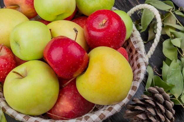 松ぼっくりと木製の表面の葉が付いているバスケットのりんごの側面図