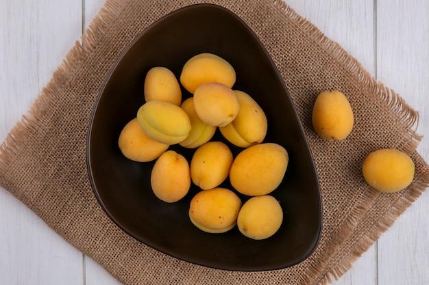 Вид сбоку абрикосов в миске на бежевой салфетке на белой поверхности