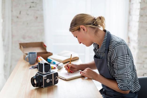 Вид сбоку художника в фартук, работающий на столе