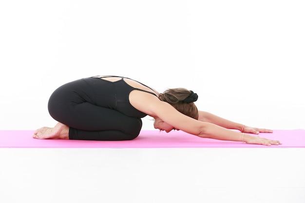 Азиатская женщина, делающая позу уттхита баласана и растягивающая тело на розовом коврике во время занятия йогой на белом фоне, вид сбоку