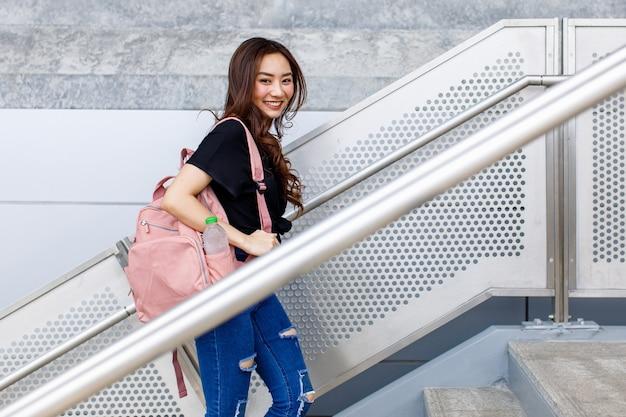 地下鉄で2階を歩いて、カメラを見ているアジアの女性の側面図