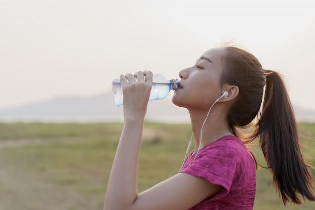 Взгляд со стороны азиатских женщин спортсмена фитнеса с водой бутылки питья и ослабляет после разминки или бежать в лете на заходе солнца или восходе солнца. концепция здоровья и образа жизни