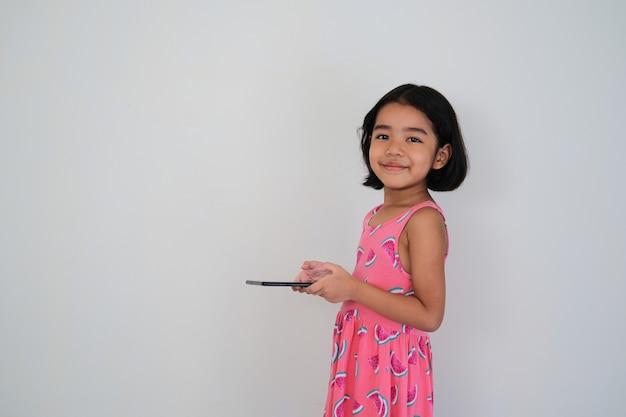 Азиатский маленький ребенок улыбается, держа в руке свой мобильный планшет, вид сбоку