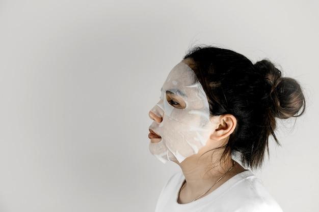 白いtシャツを着て、シートマスクで顔を覆っているアジアの女性の側面図。