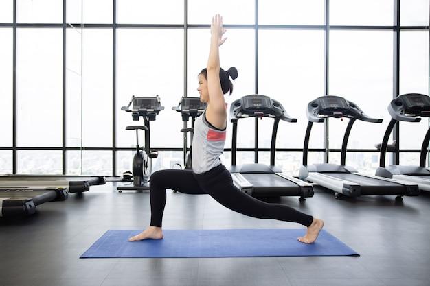 Вид сбоку азиатской женщины с воином одной позы йоги в тренажерном зале