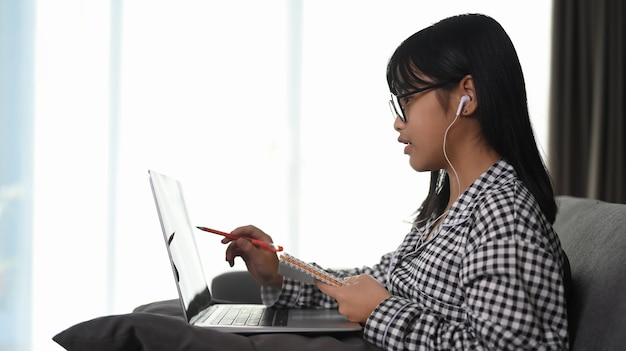 自宅でラップトップコンピューターとオンラインクラスを学ぶイヤホンを身に着けているアジアの若い女の子の側面図。