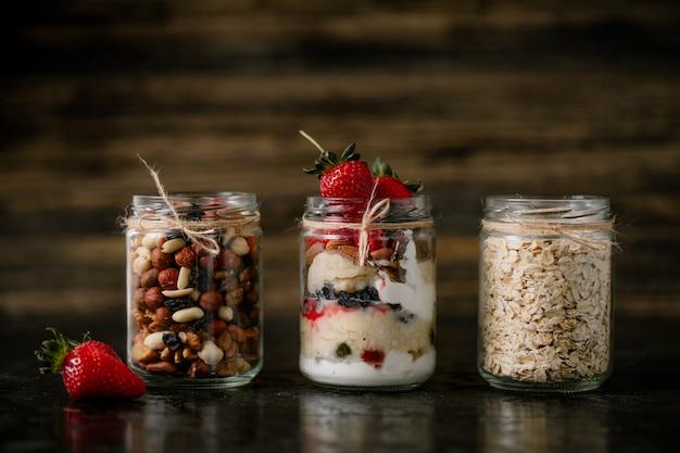 果実とナッツのオーツ麦フレークと黒い大理石のテーブルの上のガラスの瓶にミックスナッツと品揃え一晩オート麦の側面図
