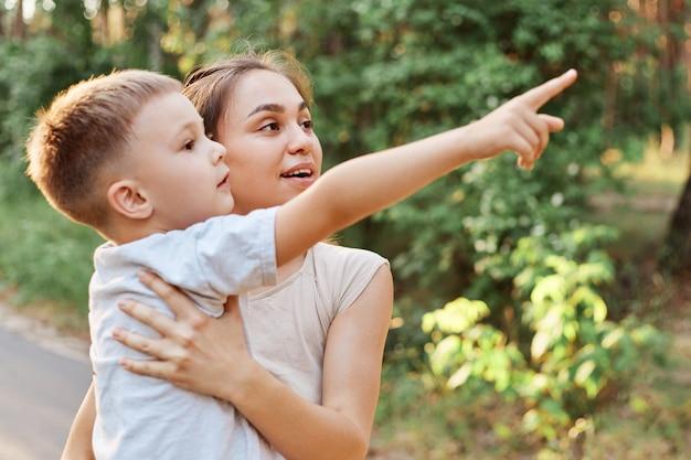 손에 아이를 들고 놀란 어머니의 측면보기, 어머니 뭔가 멀리 뭔가 보여주는 작은 아들, 손가락으로 가리키는, 놀란 표정으로 거리에서 찾고 여자.