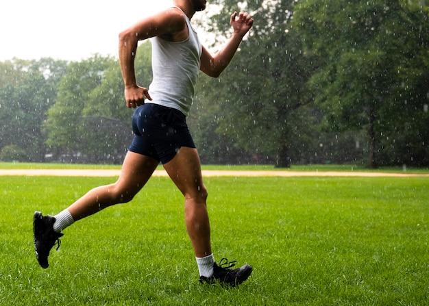 草の上を実行している運動選手の側面図