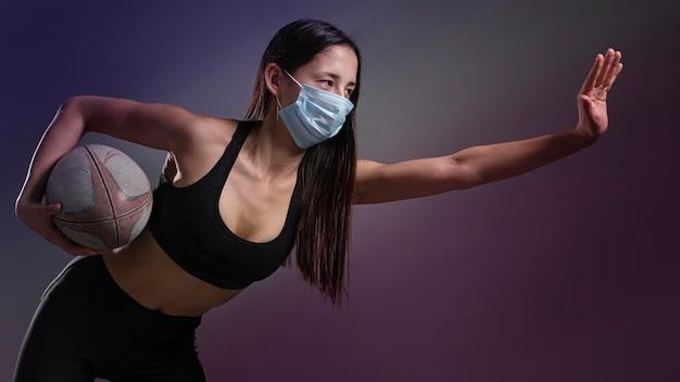 공을 들고 의료 마스크 운동 여성 럭비 선수의 측면보기