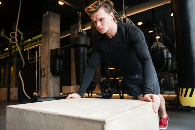 Вид сбоку спортивного человека отжимания на коробке