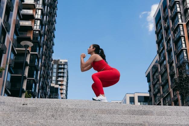 階段の上にしゃがんで暗いポニーテールを持つ運動のかわいい女の子の側面図。