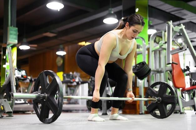 Вид сбоку спортивной женщины, осуществляющей становую тягу в тренажерном зале.