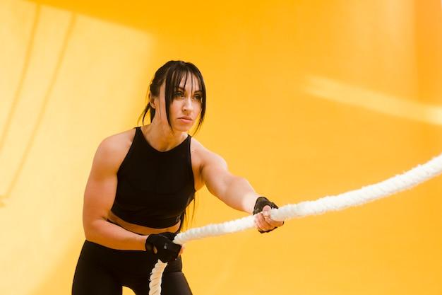 Вид сбоку спортивная женщина в тренажерном зале, потянув веревку