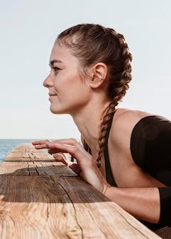 Вид сбоку спортивной женщины, готовящейся к тренировке