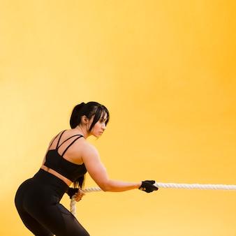 Вид сбоку спортивной женщины, потянув веревку