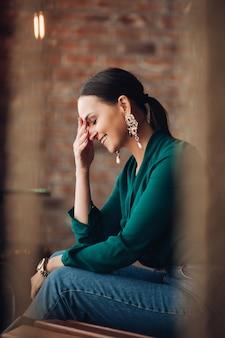 아름다운 귀걸이, 에메랄드 블라우스, 청바지를 입은 매력적인 검은 머리 여성의 측면 전망과 얼굴에 손을 대고 웃고 있는 세련된 시계. 그녀는 실내 벽돌 벽에 나무 벤치에 앉아 있다.