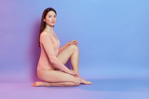 Вид сбоку привлекательной темноволосой женщины с идеальным телом, сидящей на полу на одном колене, со спокойным выражением лица, изолированной над синей стеной с розовым неоновым светом.