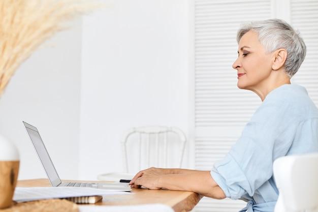 物思いにふける表情をしていて、開いているラップトップの前に座って、新しい記事に取り組んでいる魅力的な白髪の女性作家またはブロガーの側面図。電子機器でインターネットをサーフィンする年配の女性年金受給者