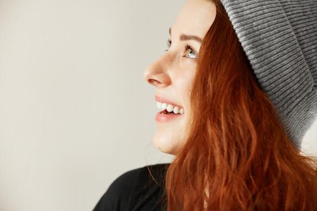 灰色の帽子に長い緩い銅色の髪を持つ魅力的な幸せな若いそばかすのある女性の側面図