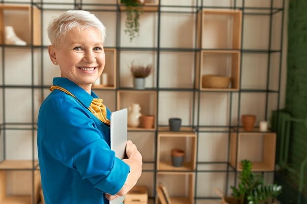 ラップトップを保持し、自宅で仕事をし、カメラで幸せそうに笑って、青いシャツを着た魅力的な楽しい中年女性の側面図。 e