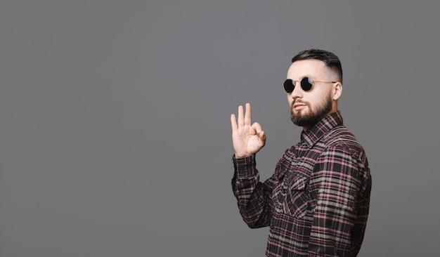 세련된 선글라스와 체크 무늬 셔츠에 매력적인 남성의 측면보기 카메라를보고 회색 배경에 서있는 동안 ok 제스처를 보여주는