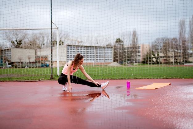 Взгляд со стороны девушки фитнеса привлекательной формы молодой протягивая ногу пока сидящ на корточках снаружи около футбольного поля.