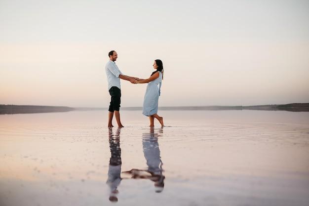 그들의 손을 잡고 해변에 서 있는 매력적인 젊은 부부의 측면 보기