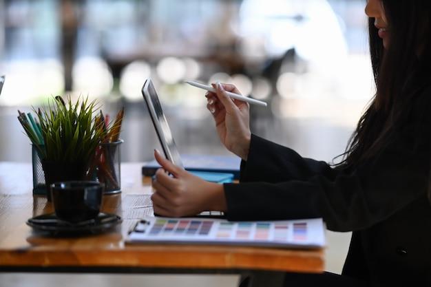クリエイティブなオフィスに座ってタブレットコンピューターで作業している魅力的な若い女性デザイナーの側面図。