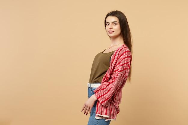 スタジオでパステルベージュの壁の背景に分離されたカメラを立って見てカジュアルな服を着た魅力的な若い女性の側面図。人々の誠実な感情のライフスタイルの概念。コピースペースをモックアップします。