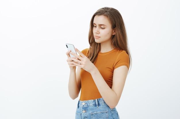 Вид сбоку привлекательной молодой женщины, обменивающейся сообщениями, смотрящей на смартфон во время редактирования фотографии с помощью мобильного приложения