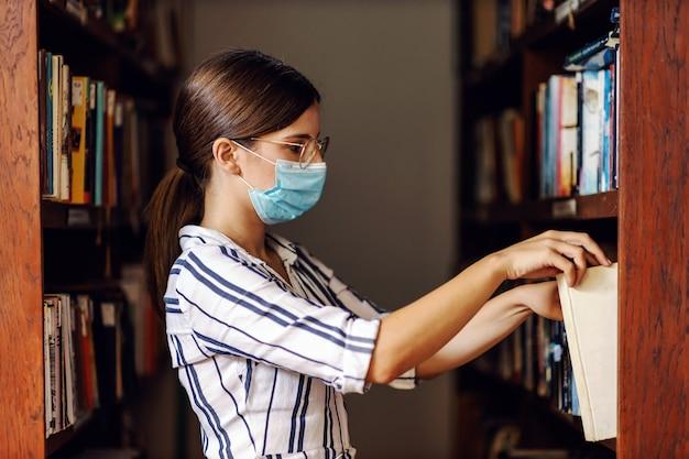 図書館に立って小説を探しているときにフェイスマスクを持つ魅力的な若い女性の側面図。 covidパンデミックの概念。
