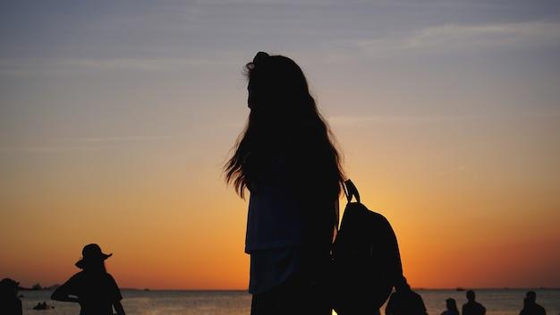 태양 앞의 여성 실루엣 따뜻한 일몰의 백라이트 측면 - 일몰 시 관광 해변