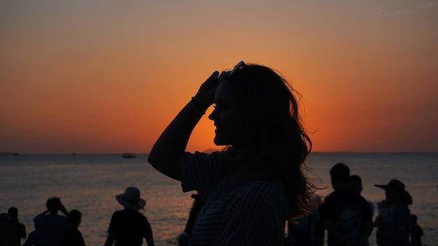 Вид сбоку заднего света силуэт женщины теплый закат перед солнцем - туристический пляж на закате