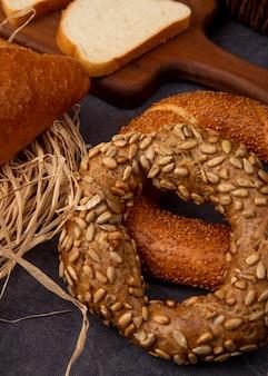 Вид сбоку бублики с ломтиком белого хлеба и соломы на бордовом фоне