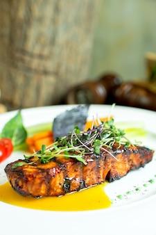 Вид сбоку на запеченный лосось с соусом наршараб на тарелке