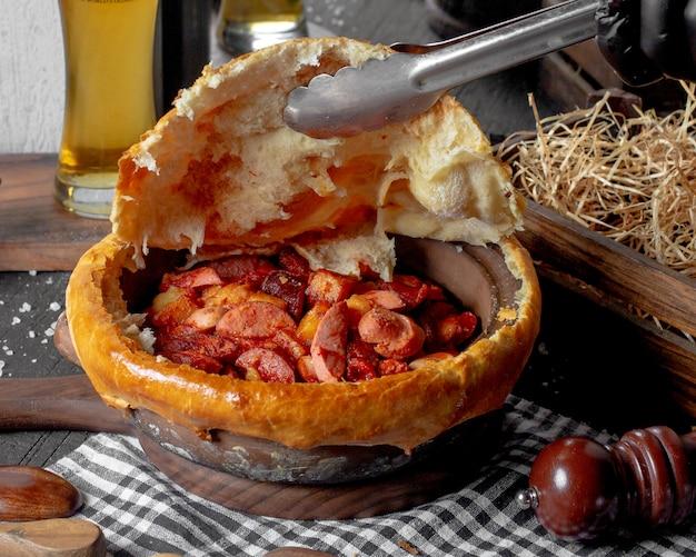 Вид сбоку запеченная колбаса в глиняной миске на деревенской поверхности