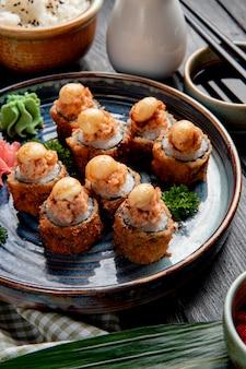 Вид сбоку на запеченные суши роллы с креветками имбирем и васаби на тарелке с соевым соусом по дереву