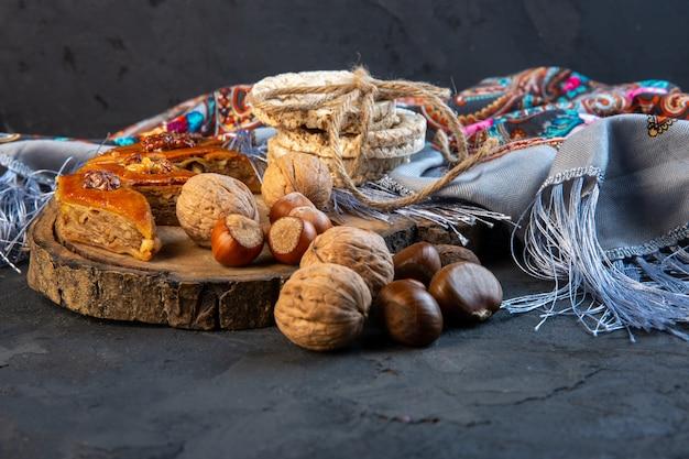 Вид сбоку на пахлаву с цельными орехами и рисовым хлебом на платке с кисточкой